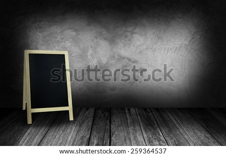 tripod blackboard in interior room with gray stone wall - stock photo
