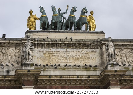 Triumphal Arch (Arc de Triomphe du Carrousel) at Tuileries gardens in Paris, France. Monument was built between 1806 - 1808 to commemorate Napoleon's military victories.  Sculptures. - stock photo