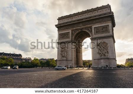 Triumphal arch in Paris city at sunset. Arc de Triomphe, Paris, France. Famous Paris view on triumphal arch. Sunset scene with sun beams going trough Triumphal arch in Paris. Paris scene. Paris Arch. - stock photo