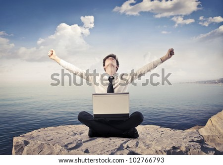 Triumphing young businessman sitting on a peak over the sea with a laptop on his knees - stock photo