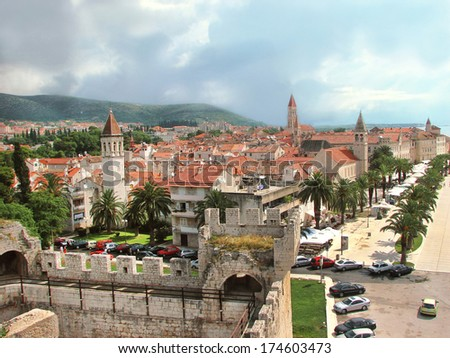 Trogir - famous historic town in Croatia (Dalmatia). Aerial view on ancient Trogir with green palms, hills and red roofs. Summer vacation concept. Outdoors. - stock photo