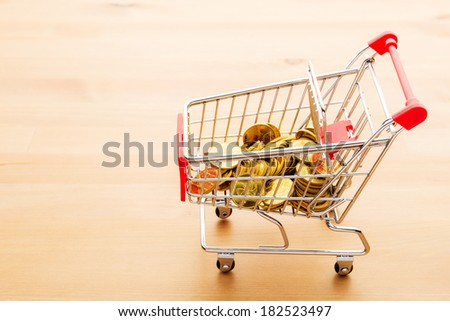 Trolley with gold coin - stock photo