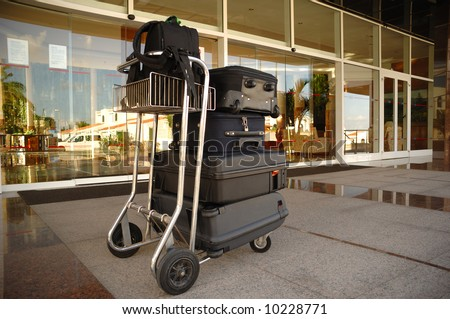 Trolley with suitcases in front of hotel - stock photo