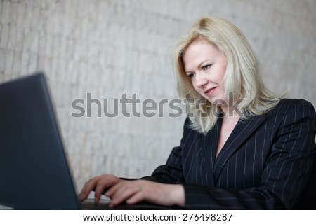 Trolling businesswoman typing on laptop in office - stock photo