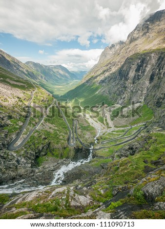 Trollstigen serpentine mountain road and Stigfossen waterfall. Part of Norwegian National Road 63 connecting Ã?Â?ndalsnes in Rauma and Valldal in Norddal. - stock photo