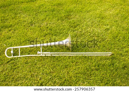 trombone instruments against grass background - stock photo