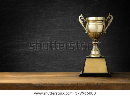 Trophies placed on a wooden table with blackboard background  - stock photo