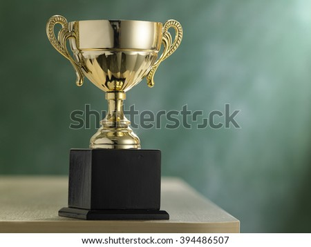 trophy in front of blackboard with light ray effect - stock photo