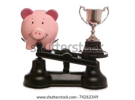 Trophy out weighing piggybank studio cutout - stock photo