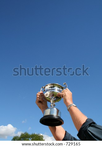 Trophy won held proudly aloft to a Blue sky and photographer seen in reflection - stock photo