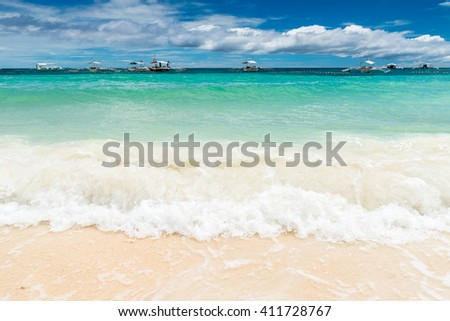 Tropical background view from Paglao island at Alona beach with traditional boats, waves and blue sky and turquoise sea water Travel Vacation at Philippines - stock photo