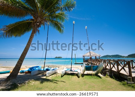 Tropical beach and pier.  Water activities - stock photo