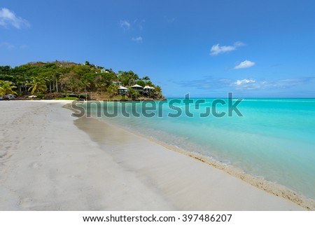 Tropical beach at Antigua island in Caribbean with white sand, turquoise ocean water and blue sky - stock photo