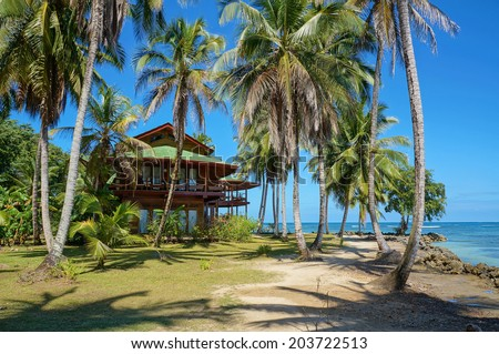 Tropical beach house with coconut palm trees on an island in the Caribbean - stock photo