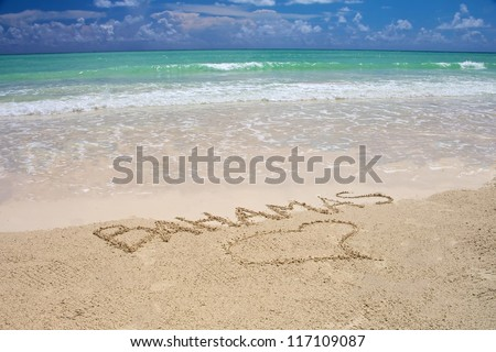 Tropical beach in Bahamas with bright blue sky, turquoise water and writing on the sand - stock photo