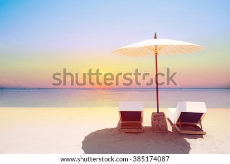 Tropical beach in sunset with beach chairs and umbrella - stock photo