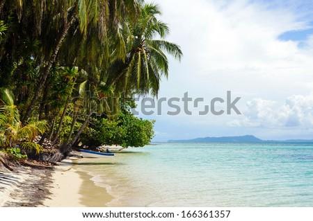 Tropical beach island with leaning coconut tree and a boat, Caribbean sea, Zapatillas Keys, Panama - stock photo