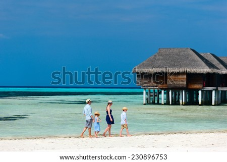Tropical beach landscape with a beautiful family of four enjoying luxury summer vacation - stock photo