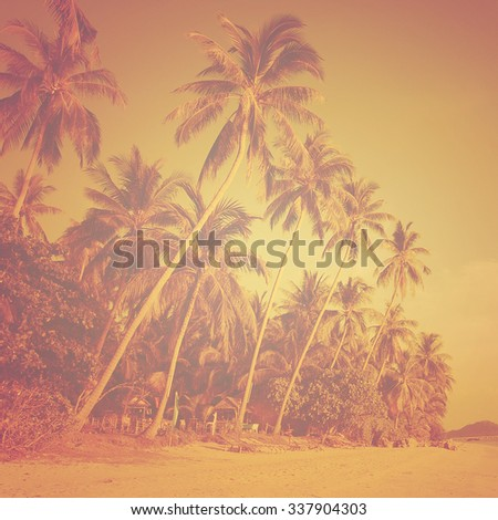 Tropical beach landscape with coconut palm trees at sunset. Paradise design banner background. Vintage (instagram) effect. Old-fashioned retro image. - stock photo