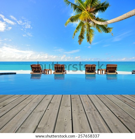 Tropical beach resorts swimming pool overlooking the sea -- Tropical beach vacation and travel concept - stock photo