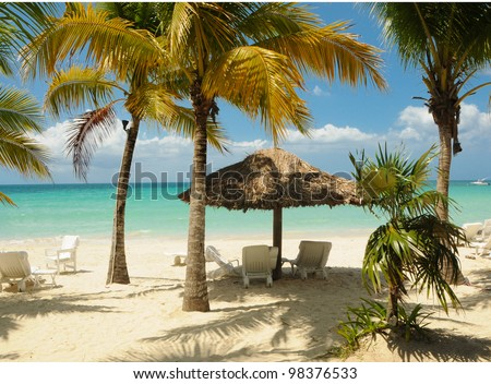 Tropical Beach Setting with Palm Trees, Hut and chairs. - stock photo