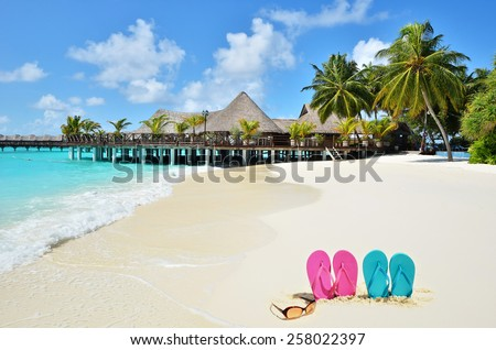 Tropical beach vacation and travel concept -- Sunglasses and flip flops at the beach   - stock photo