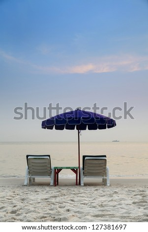 Tropical beach with chairs and parasol in thailand - stock photo