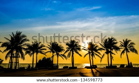 Tropical beach with coconut palm on sunset background - stock photo