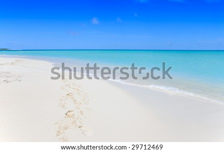tropical beach with footprints in the sand - stock photo