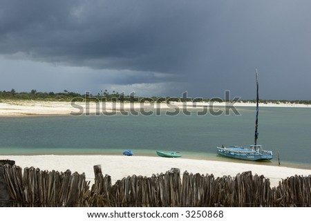 Tropical beach with stormy sky - stock photo