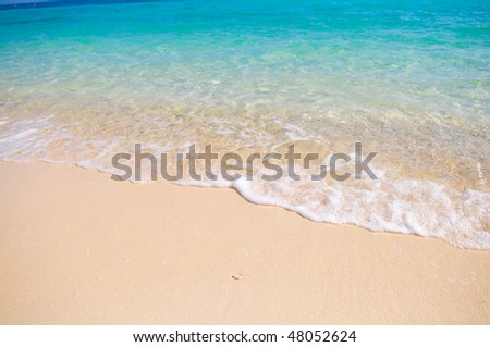 Tropical beach with white coral sand and calm wave - stock photo