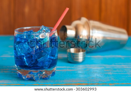 tropical blue cocktail served on a out of focus bar. With defocused metal shaker on background. - stock photo