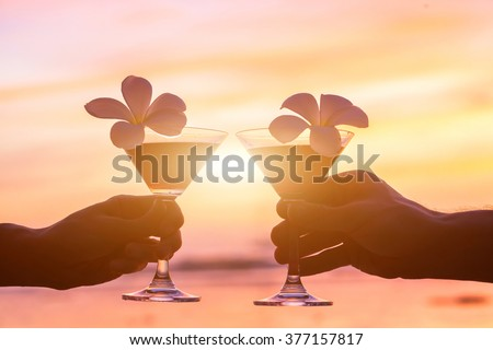 tropical cocktails on the beach, couple of hands with glasses - stock photo
