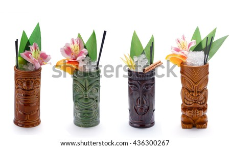 Tropical cocktails served in a tiki style glass and garnished with fruits - stock photo
