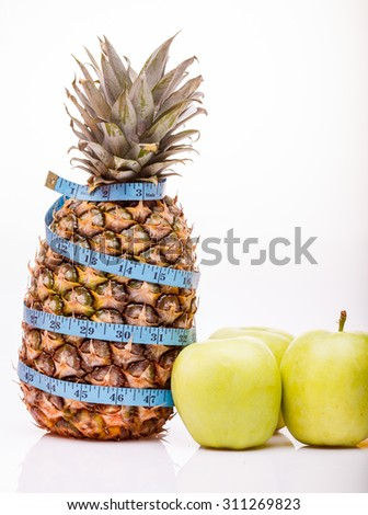 Tropical fresh fruits of one big pineapple and green ripe apples with blue measuring tape as diet symbol on white studio background closeup copyspace, vertical picture - stock photo