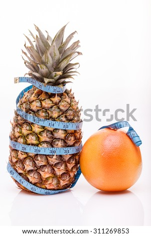 Tropical fresh fruits of one big pineapple and orange juicy grapefruit with blue measuring tape as diet symbol on white studio background closeup copyspace, vertical picture - stock photo