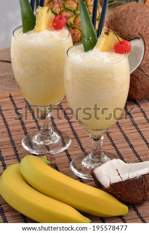 Tropical fruit cocktail drinks and banana. - stock photo