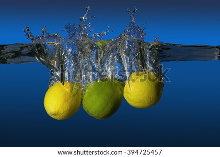 tropical fruit limes and lemons dropped in water - stock photo