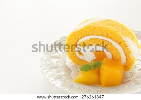 Tropical fruit Mango and Swiss roll - stock photo
