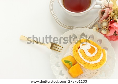 Tropical fruit Mango and Swiss roll with English tea on background - stock photo