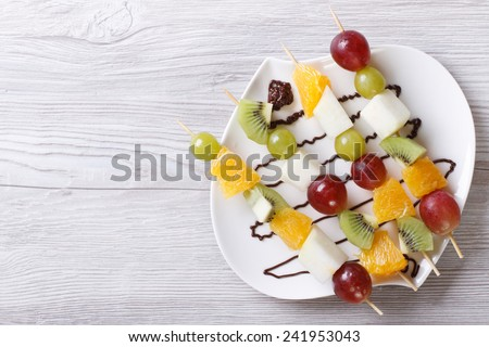 Tropical fruit on skewers with chocolate sauce. horizontal view from above  - stock photo