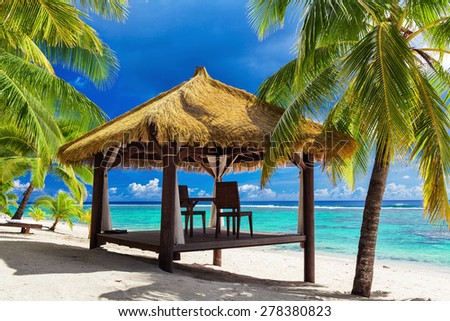 Tropical gazebo and two chairs on an sandy island beach with coconut palm trees - stock photo