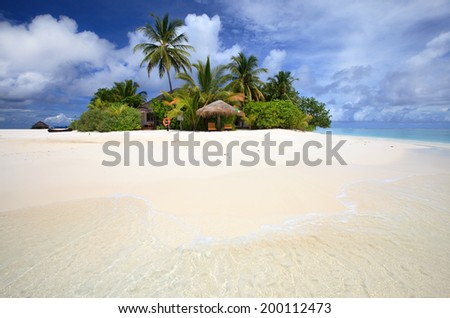 Tropical green island resort in the Indian Ocean. Beautiful white sandy beach is surrounding the island. It is perfect place for relaxing  vacation and honeymoon.  - stock photo