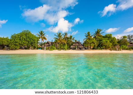 Tropical island beautiful landscape with emerald water, green trees and blue sky - stock photo