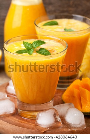Tropical lemonade with mango, pineapple and mint in glasses and bottle on old wooden background - stock photo