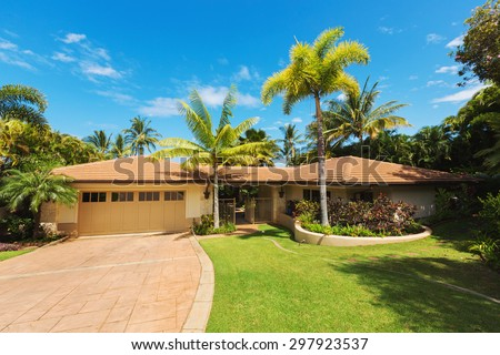 Tropical Luxury Home, Exterior View with Green Lawn and Driveway - stock photo