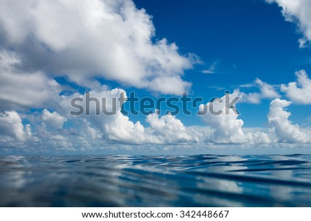 Tropical ocean with bright water and reflections. Maldivian paradise with clouds on blue sky in daylight. - stock photo