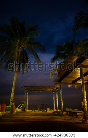 Tropical pavilion with chairs on amazing beach with mpal tree at night in thailand. - stock photo
