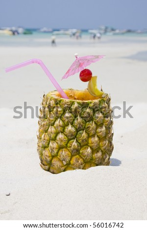Tropical pineapple cocktail drink at the beach overlooking the ocean - stock photo
