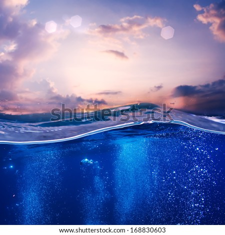 Tropical postcard sea water design template. Beautiful sunset at the sea nice pink clouds and blue water with air bubbles - stock photo